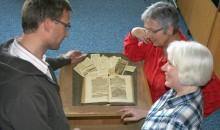Beate Dixius und Claudia Kuhnen (v.r.n.l.) vom Verein der Gästeführer Trier und Region e.V. begutachten zusammen mit dem Bibliothekar Ted Schirmer einen Stadtführer aus dem 17. Jahrhundert, der durch die Trierer Spenden zum Weltgästeführertag 2013 restauriert werden konnte