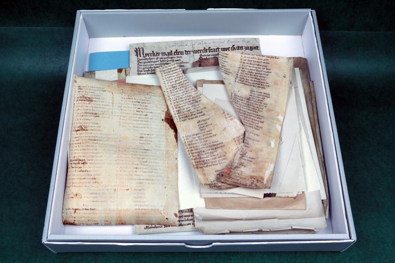 Blick in die alte Fragmentenbox. Die Fragmente lagern in Briefumschlägen oder zwischen säurehaltigen Papieren. Sie sind ungeschützt und belasten sich gegenseitig mechanisch, was zu irreparablen Schäden am Trägermaterial führt.